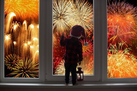 Toddler child standing in front of a big french doors, leaning against it looking at new years eve fireworks, holding lantern