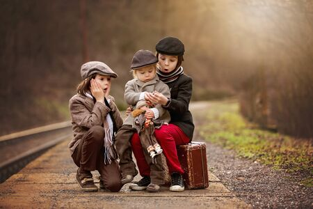 Adorable boys on a railway station, waiting for the train with suitcase and beautiful vintage porcelain doll Reklamní fotografie