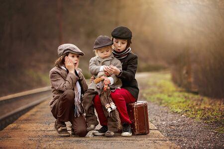 Entzückende Jungs auf einem Bahnhof, die mit Koffer und schöner Vintage-Porzellanpuppe auf den Zug warten Standard-Bild