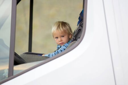 Cute toddler boy, kid sitting on the front seat in child seat on big camper van, smiling happily Archivio Fotografico - 137433643