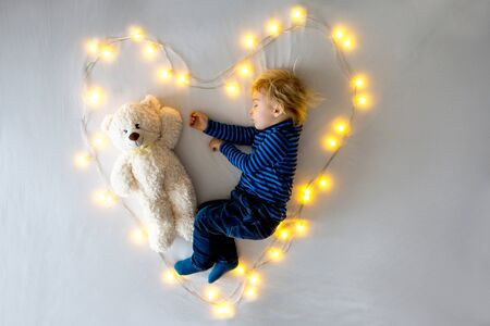 Little baby boy, sleeping with teddy bear in bed in heart made by light string