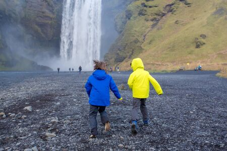 Cute child playing in front of the Skogafoss waterfall in Iceland on a sunset cloudy day, autumntime