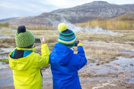 Children, taking picture of Strokkur Geysir while erupting, Iceland autumntime