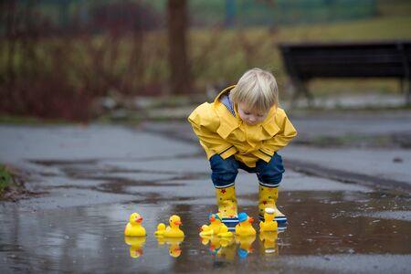 Schöner lustiger blonder Kleinkindjunge mit Gummienten und buntem Regenschirm, der in Pfützen springt und im Regen spielt, Winterzeit