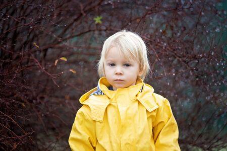 Bello e divertente bambino biondo, che guarda le gocce di pioggia su un ramo di un albero, gioca sotto la pioggia, in inverno