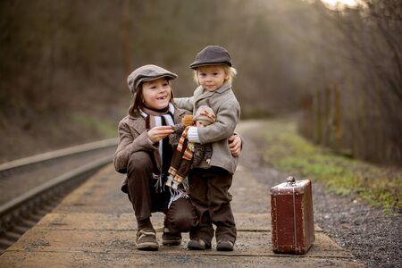 Entzückende Jungs auf einem Bahnhof, die mit Koffer und schöner Vintage-Porzellanpuppe auf den Zug warten