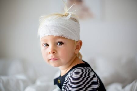 Close portrait of little toddler boy with head injury, sitting in bed, tired, looking at camera