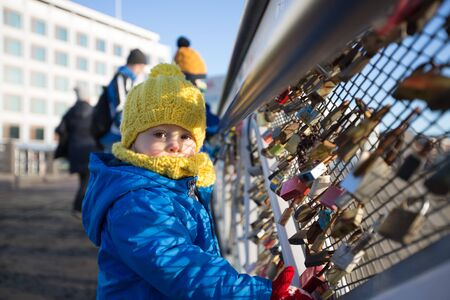 Cute toddler child, looking at love locks, locked on a bridge fence in Helsinki