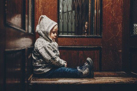 Sweet toddler blonde boy, sitting in an old wooden elevator or lift with grating