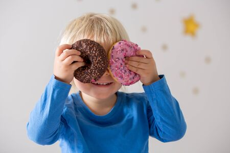 Cute sweet blonde child, playing and eating donuts at home