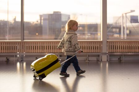 Blonde toddler boy with family, traveling with airplane, running at the airport with suitcase
