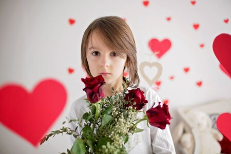 Cute long haired school boy, holding heart box and red roses for Valentine, child experiencing first love