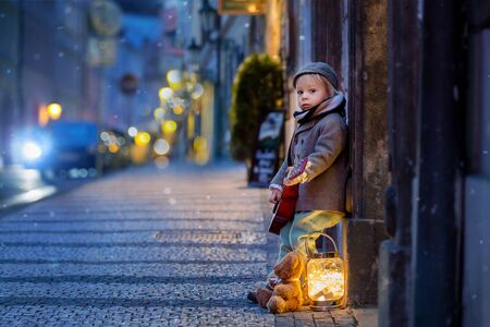 Sweet toddler boy, playing guitar at night in the city with teddy bear toy ang lights