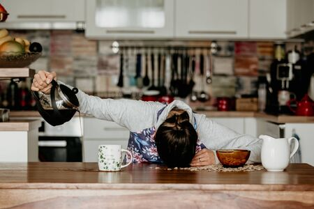 Tired mother, trying to pour coffee in the morning. Woman lying on kitchen table after sleepless night, trying to drink coffee Stock Photo