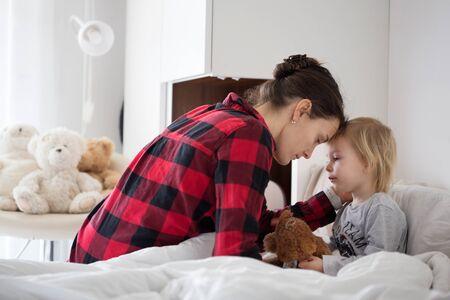 Mère et bébé tôt le matin, maman prenant soin de son petit garçon malade. Bébé au lit avec fièvre et nez qui coule Banque d'images
