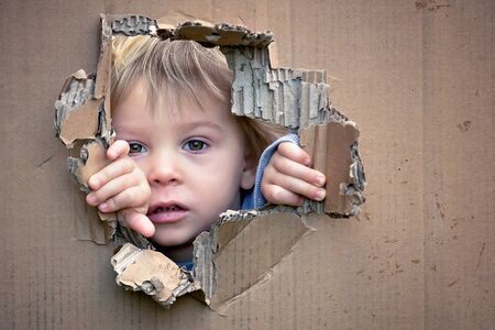 Sweet toddler child, cute blond boy, hiding in cardboard box, looking out from a hole, smiling