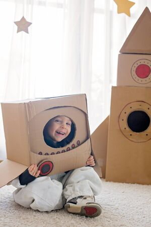 Sweet toddler boy, dressed as an astronaut, playing at home with cardboard rocket and handmade helmet from box Standard-Bild