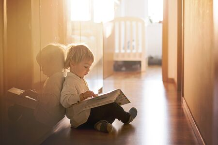 Beautiful toddler blond boy, lying on the floor at home in the hall, reading book, beautiful back light Stock fotó