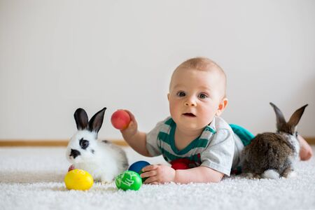 Little toddler child, baby boy, playing with bunnies and easter eggs at home, colorful hand drawings on the eggs