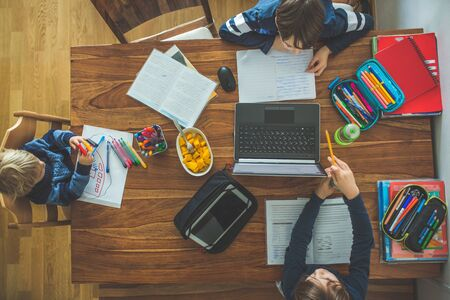 Three children, sitting around the table, writing school tasks while homeschooling, while school closed due to Coronavirus Zdjęcie Seryjne