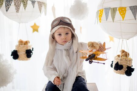 Cute little child, boy, playing with chicks at home, pretending that he is flying in the sky, pilot with plane and pet chick