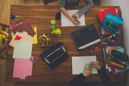 Three children, sitting around the table, writing school tasks while homeschooling, while school closed due to Coronavirus
