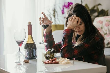 Sad tired woman, drinking wine at home, alone, sitting on the floor in living room, feeling depressed