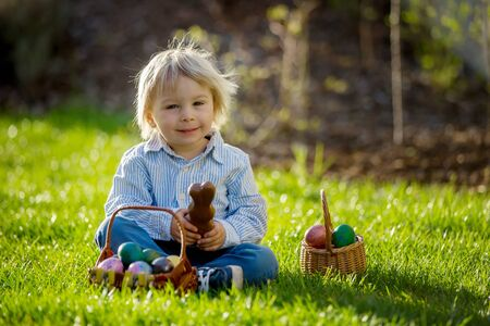 Little toddler boy, eating chocolate bunny in garden on sunset, easter eggs around him