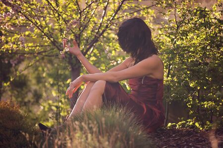 Young woman with red dress, sitting in garden on sunset