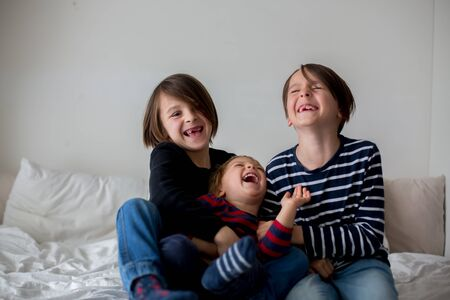 Three children, boy brothers, laughing in bed, gigling and tickling
