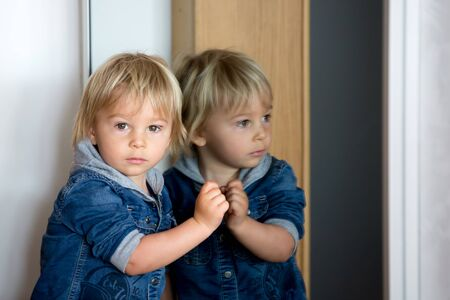 Reflection of a cute little toddler boy, child, looking in mirror, indoors