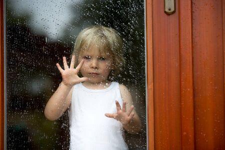 Sad child behind the window on a rainy day