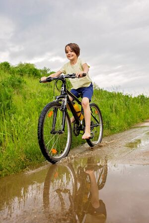 Child, boy, riding bike in muddy puddle, summer time on a rainy day