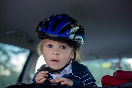 Child with helmet, toddler boy,  riding in car after riding bike on summer evening