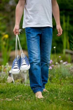 Preteen child, holding pair of sneakers in his hands, walking on a rural path, barefeet Stock Photo