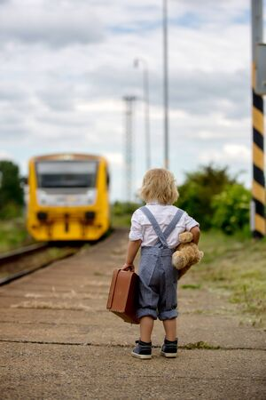 Sweet toddler child with teddy bear, book and vintage suitcase waiting for the train on a train station, going on summer holiday