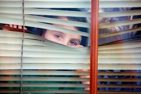 Child, toddler boy, looking through window outside Stockfoto