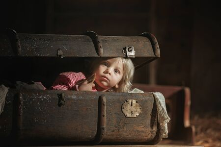 Little child, boy, hiding in old vintage suitcase in the attic, scared not to be found Фото со стока - 150511674