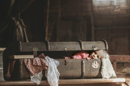 Little child, boy, hiding in old vintage suitcase in the attic, scared not to be found Фото со стока - 150511679