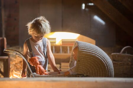 Little toddler boy, playing with doll stroller and baby doll in attic, nice soft light Фото со стока