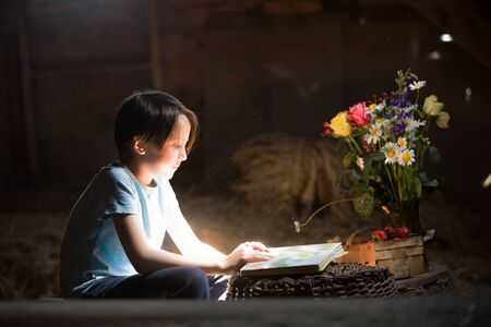Little preschool boy, reading a book in the attic, nice atmosphere, flowers and strawberries next to him
