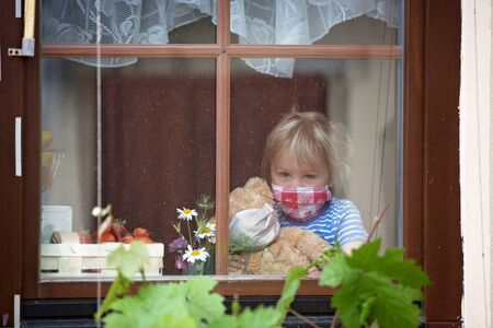 Sweet toddler boy, wearing medical mask, hugging teddy bear, also with mask, looking sadly out of the window, during coronavirus pandemic isolation Фото со стока