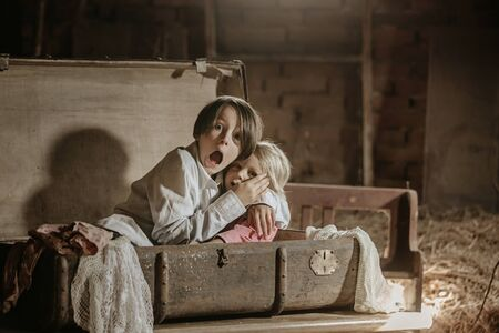 Little child, boy, hiding in old vintage suitcase in the attic, scared not to be found