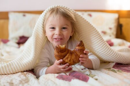 Cute blonde toddler child,reading book and eating croissant in bed, laughing happily Фото со стока
