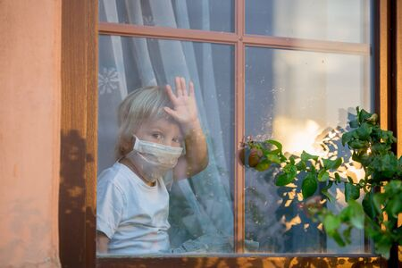 Little toddler child, boy, sitting sad on a window shield, looking outside at sunset, wearing protective medical mask, isolated due to coronavirus
