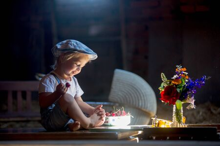 Cute beautiful child, blond kid, reading book and playing with construction blocks in a cozy attic room, filled with light