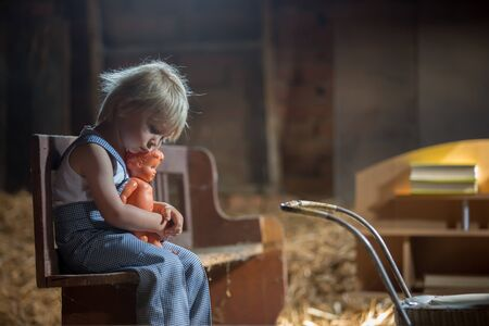 Little toddler boy, sitting on old vintage bench, holding doll and playing in the attic Archivio Fotografico