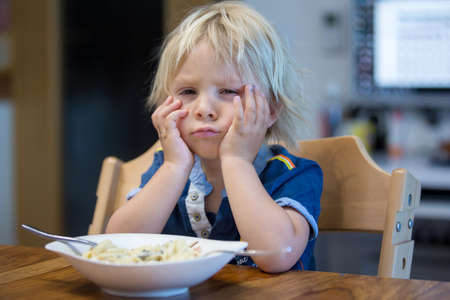 Cute blond boy, child eating spaghetti with hands at home Фото со стока