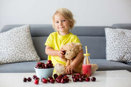 Toddler blond child, cute boy, eating cherries with teddy bears at home Фото со стока