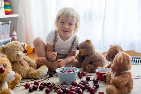 Toddler blond child, cute boy, eating cherries with teddy bears at home Фото со стока - 151059000